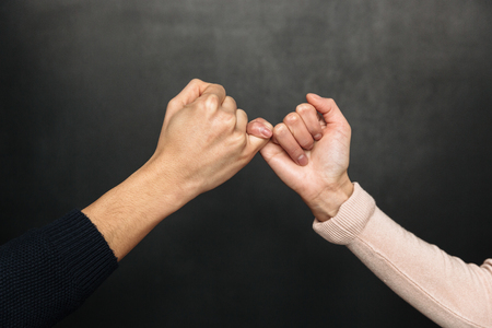 Cropped image of Asian couple holding pinkies to each other over black background Stock Photo