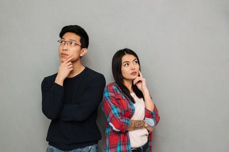 Bild des Denkens ernstes junges asiatisches liebendes Paar, das lokalisiert über grauem Wandhintergrund steht, der beiseite schaut.