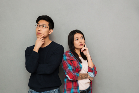 Image of thinking serious young asian loving couple standing isolated over grey wall background looking aside. 免版税图像