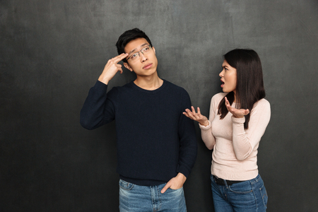 Confused asian man showing gun gesture while listening his girlfriend which quarrels with him over black background