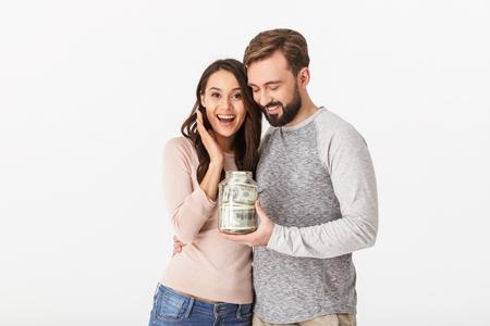 お金で瓶を保持している白い壁の背景の上に孤立した幸せな若い愛情のあるカップルのイメージ。 写真素材 - 101653291