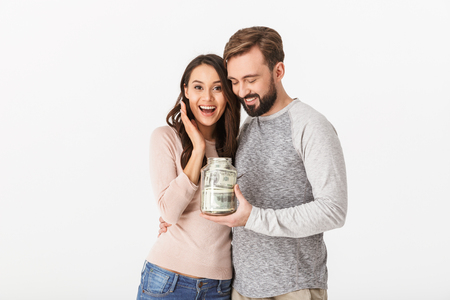 Image of happy young loving couple isolated over white wall background holding jar with money.