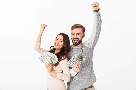 Photo of happy young loving couple standing isolated over white background holding money make winner gesture looking camera. Banco de Imagens