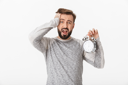 Photo of screaming scared young man isolated over white wall background holding alarm clock. Stockfoto