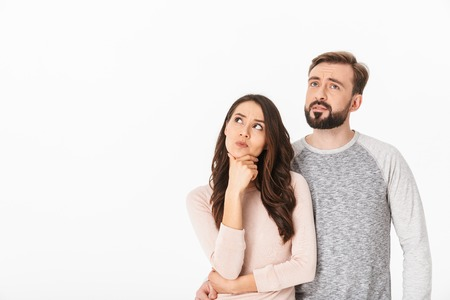 Imagen de pensamiento serio joven pareja amorosa aislada sobre fondo de pared blanca mirando a un lado.