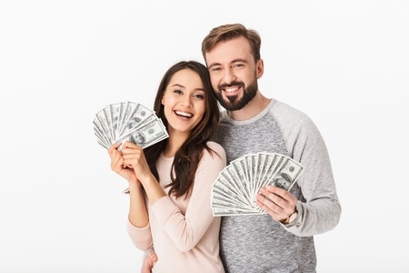 Photo of happy young loving couple standing isolated over white background holding money.