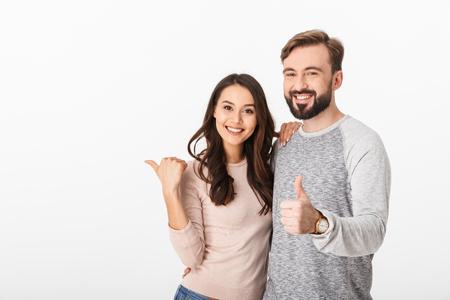 Bild des fröhlichen jungen liebenden Paares lokalisiert über weißem Wandhintergrund. Schauende Kamera zeigt Daumen hoch.