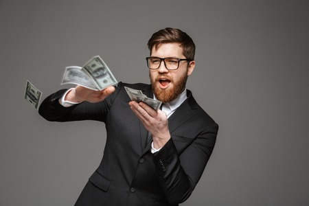 Portrait of a happy young businessman throwing out money banknotes isolated over gray background 免版税图像