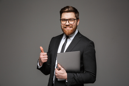 Portrait of a smiling young businessman dressed in suit holding laptop computer and showing thumbs up isolated over gray background