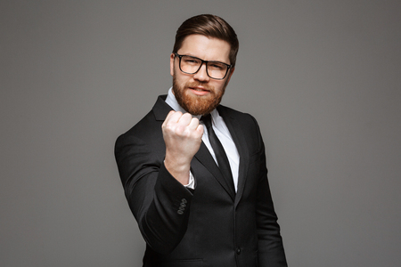 Portrait of an angry young businessman dressed in suit threatening with fist isolated over gray background Stock Photo