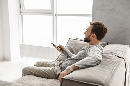 Portrait of a smiling young man holding TV remote control while sitting on a couch at home