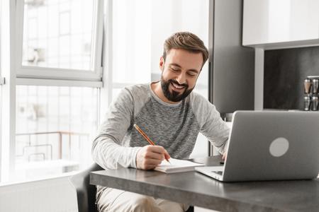 Portret van een glimlachende jonge man die op laptop computer werkt en notities maakt terwijl hij thuis aan de tafel zit