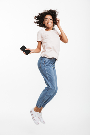 Full length image of happy african american woman with brown curly hair wearing jeans and t-shirt levitating with smartphone in hand isolated over white background