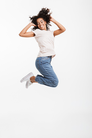 Full length portrait of adorable american woman with afro hairstyle wearing jeans and t-shirt jumping and rejoicing with perfect smile isolated over white background Stock Photo