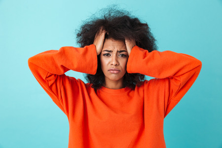 Image closeup of frustrated woman in red shirt looking on camera and grabbing head with shaggy hair isolated over blue background