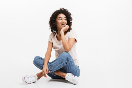 Portrait of smiling young afro american woman resting while sitting on a floor with legs crossed isolated over white background Stock Photo