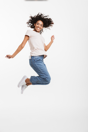 Full length portrait of satisfied american woman wearing jeans and t-shirt jumping and rejoicing with perfect smile isolated over white background