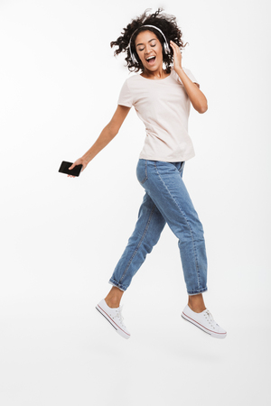 Full length image of satisfied african american woman taking pleasure while listening to music using wireless headphones and smartphone isolated over white background