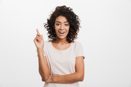 Portrait of a happy young afro american woman pointing finger up isolated over white background