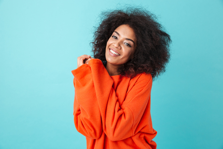 Colorful portrait of african american woman in red shirt with afro hairstyle looking on camera with smile pressing her arms to chest isolated over blue background