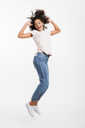 Full length image of attractive african american woman with brown curly hair wearing jeans and t-shirt posing with pleasant smile isolated over white background