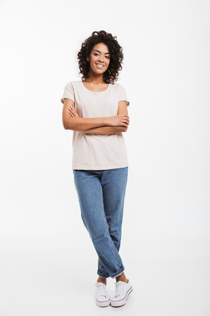 Full length portrait of beautiful american woman wearing jeans and t-shirt standing with arms folded and smile isolated over white background Banque d'images