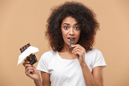 Porträt einer fröhlichen jungen afrikanischen Frau, die Schokoriegel lokalisiert über beigem Hintergrund isst Standard-Bild - 101853215