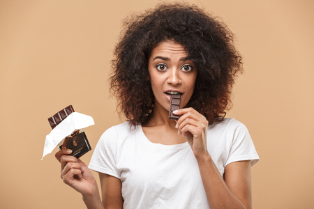 Portrait of a cheerful young african woman eating chocolate bar isolated over beige background