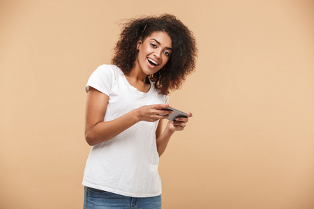 Portrait of a cheerful young african woman playing games on mobile phone isolated over beige background