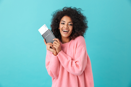 Portrait of happy excited woman 20s with afro hairstyle rejoicing and holding passport with tickets isolated over blue background