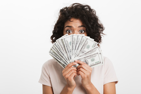 Photo of surprised american woman with afro hairstyle covering face with fan of money dollar bills and looking on camera isolated over white background Reklamní fotografie