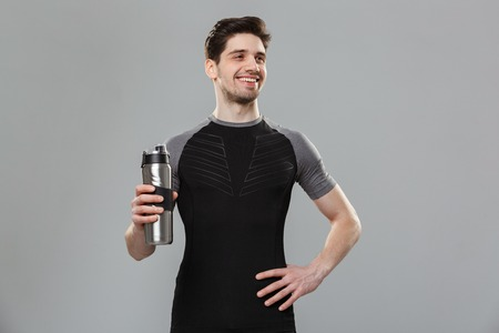 Portrait of a cheerful young sportsman holding water bottle isolated over gray background