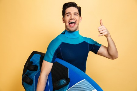 Portrait of a happy young man dressed in swimsuit showing surf gesture while holding a surfboard isolated over yellow background