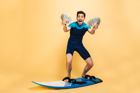 Full length portrait of an excited young man dressed in swimsuit holding bunch of money banknotes while surfing on a board isolated over yellow background Stock Photo