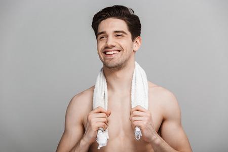 Ritratto di bellezza del giovane mezzo sorridente che tiene l'asciugamano sulle spalle isolato sopra priorità bassa grigia