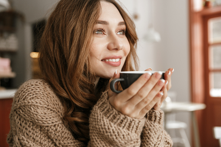 Portrait closeup of glad smiling woman with brown curly hair resting in cafe and drinking cup of tea or coffee Stock Photo