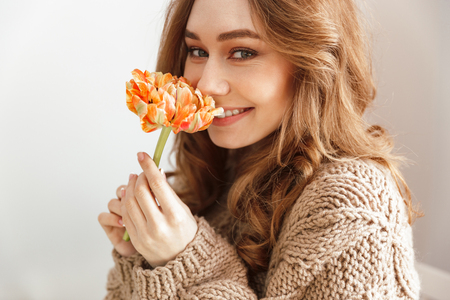 Photo of lovely woman in sweater sitting at table in cafe looking on camera with smile and smelling flower Stok Fotoğraf - 103766998