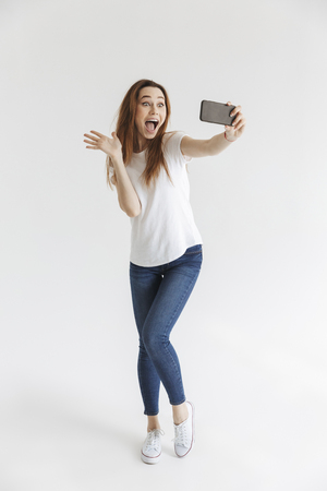 Full length image of Joyful woman in casual clothes posing and making selfie on smartphone while waving at camera over grey background Banco de Imagens