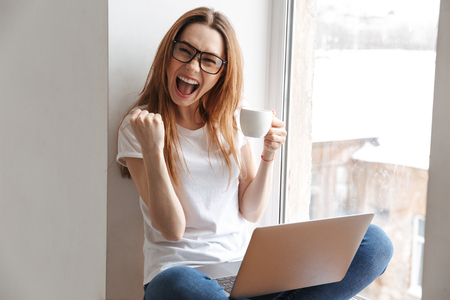 Cheerful woman in t-shirt and eyeglasses sitting on windowsill with cup of coffee and laptop computer while rejoices and looking at the camera Stock Photo