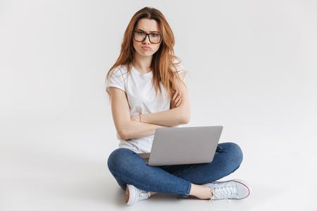 Offensé femme en t-shirt et lunettes assis sur le sol avec un ordinateur portable tout en regardant la caméra avec les bras croisés sur fond gris
