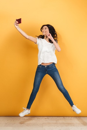 Image of cute young pretty woman jumping isolated over yellow background make selfie by phone with peace gesture.