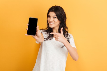 Image of young pretty woman standing isolated over yellow background looking camera showing display of mobile phone.