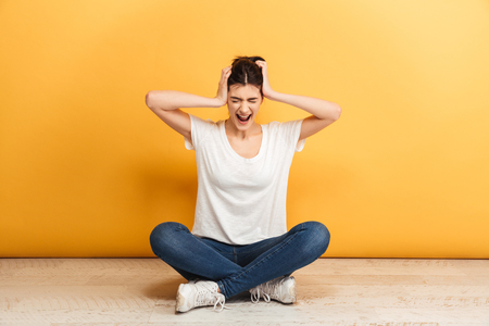 Portrait of a annoyed young woman sitting with legs crossed on a floor and screaming over yellow background