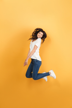 Image of young emotional woman jumping isolated over yellow background. Looking camera.
