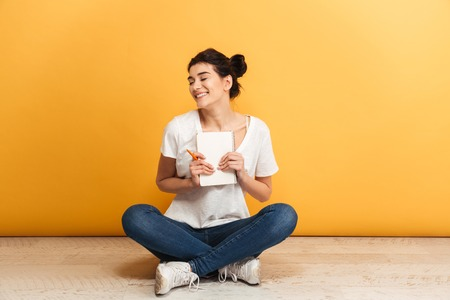 Portrait of a cheerful young woman holding a notebook while sitting with legs crossed on a floor over yellow background