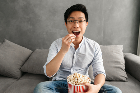 Portrait of a happy young asian man eating popcorn while sitting on a couch at home and watching TV