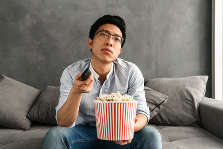 Portrait of a bored young asian man holding popcorn and TV remote control while sitting on a couch at home