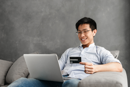 Portrait of a happy young asian man using laptop computer at home. Looking aside sitting on sofa holding credit card. Stockfoto