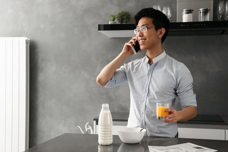 Portrait of a smiling young asian man talking on mobile phone while having breakfast on a kitchen at home Banque d'images
