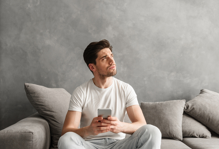 Image of man in basic t-shirt holding cell phone in hands and looking aside with brooding gaze while sitting on couch in living room Stock Photo